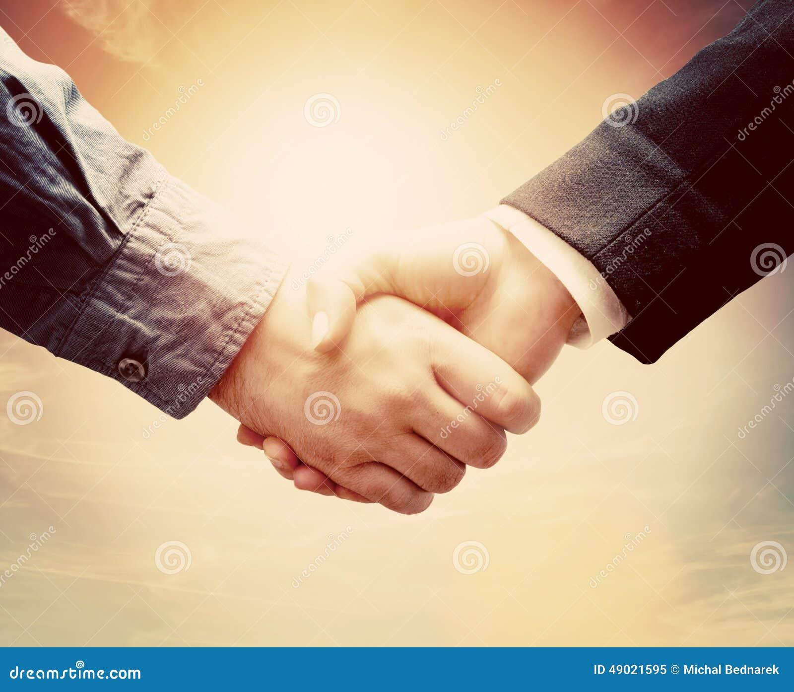 business people handshake  sunny vintage sky stock photo