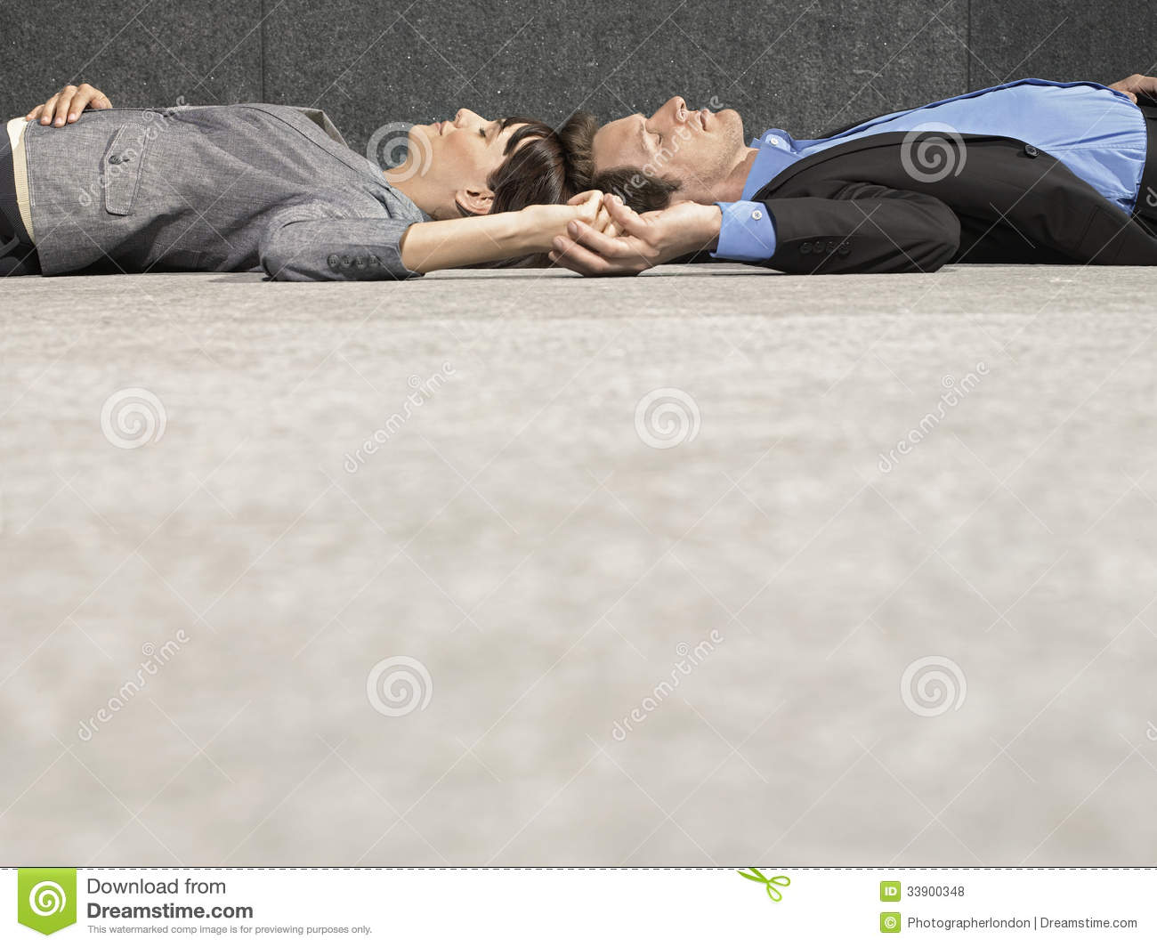 Technology Management Image: Business People Holding Hands While Lying On Ground Stock