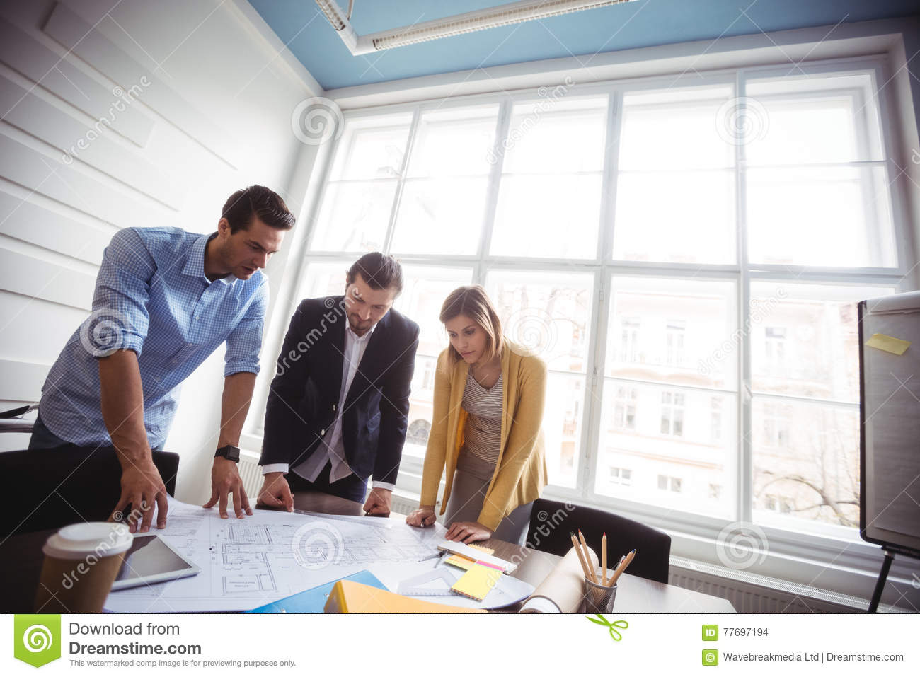 Business people looking at blueprint on table stock photo image of download business people looking at blueprint on table stock photo image of colleagues explaining malvernweather Images