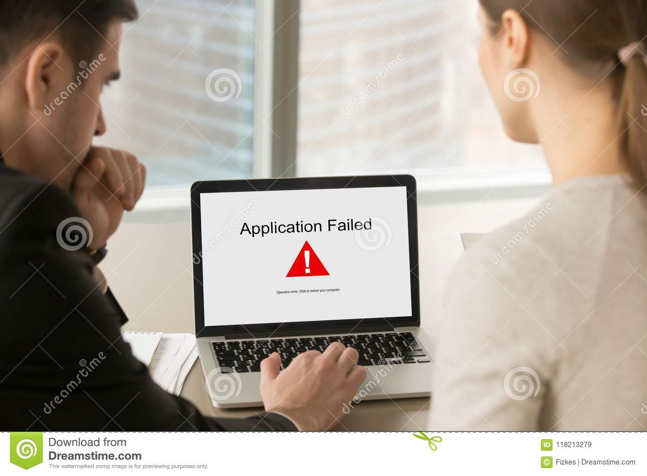 Business people looking at laptop screen with Application Failed