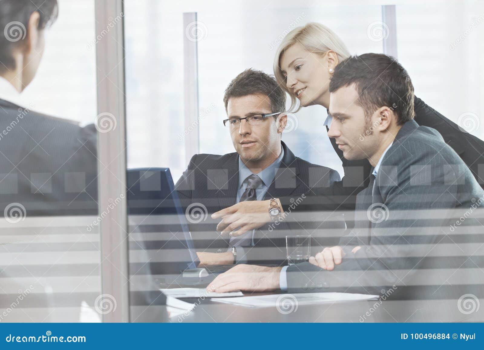 Business people meeting in boardroom behind glass