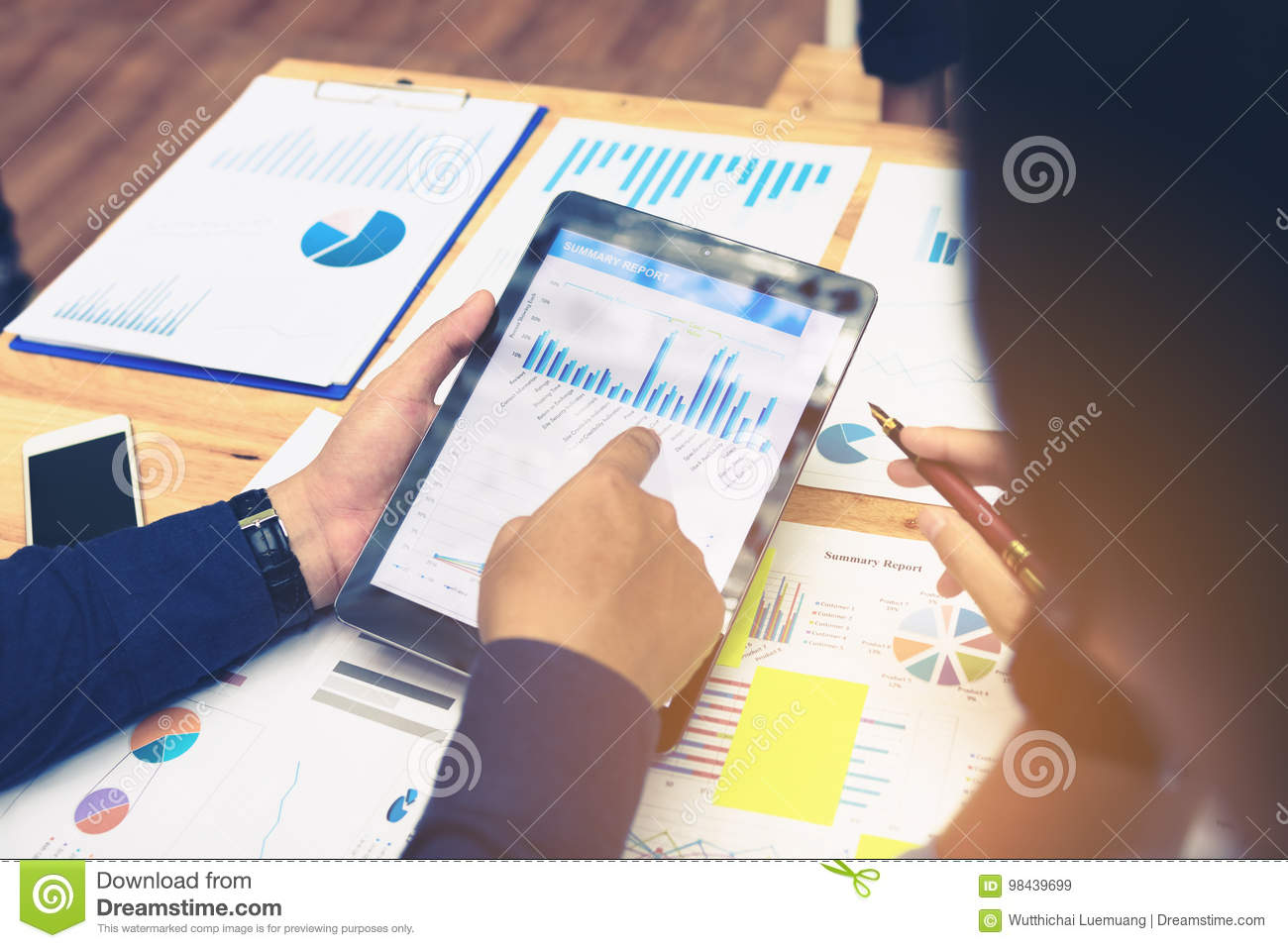 Business people pointing to tablet screen to looking graphs summary with earnings result data.