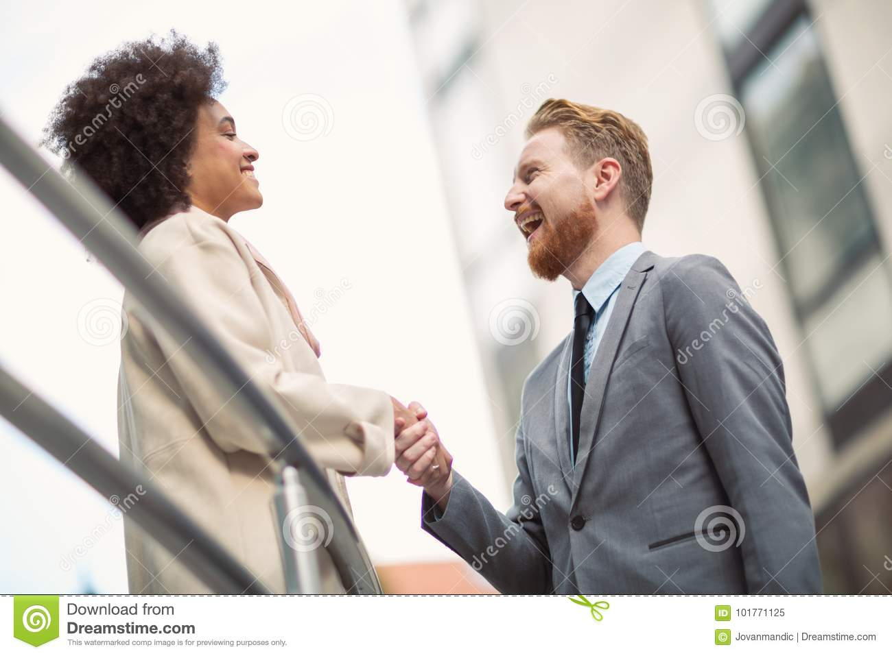 Business people shaking hands on city street