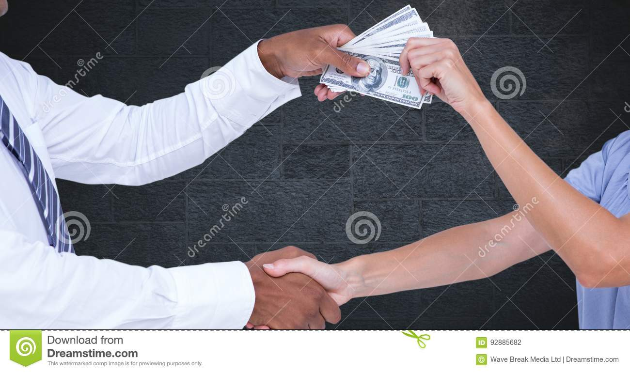 Business people shaking hands while holding money representing corruption concept