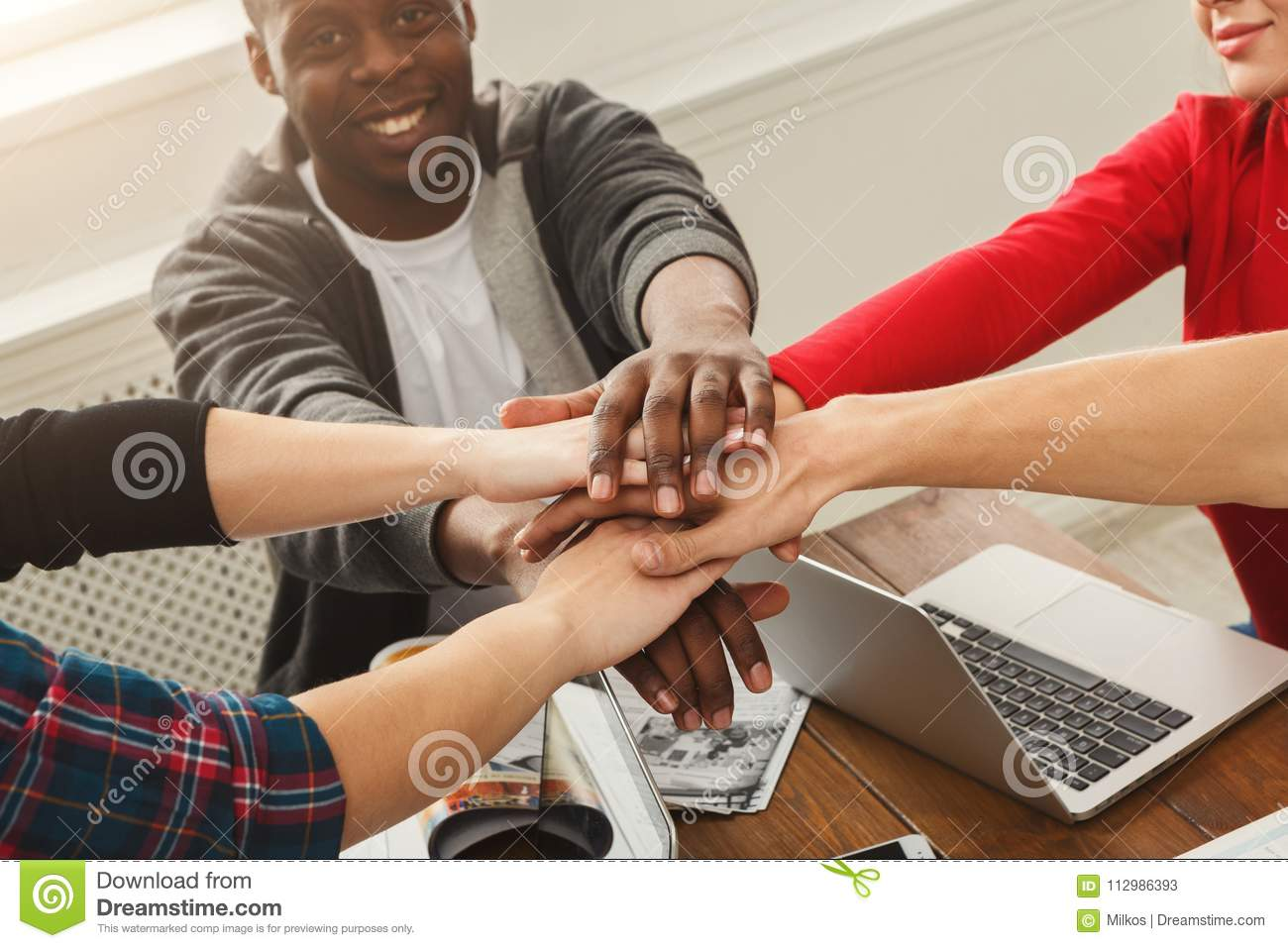 Business people at working table putting hands together