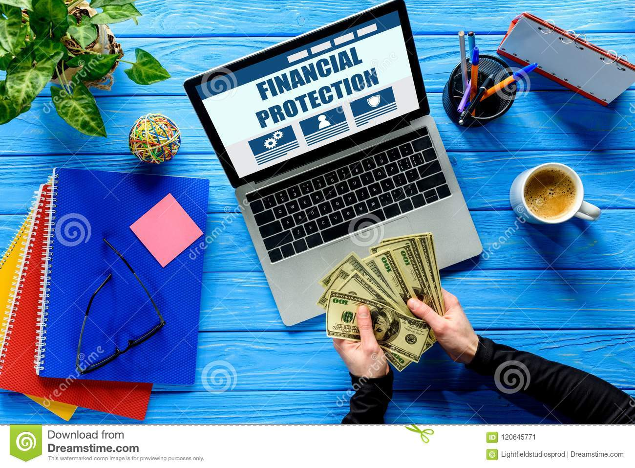Business person counting dollars by laptop on blue wooden table with stationery, Financial