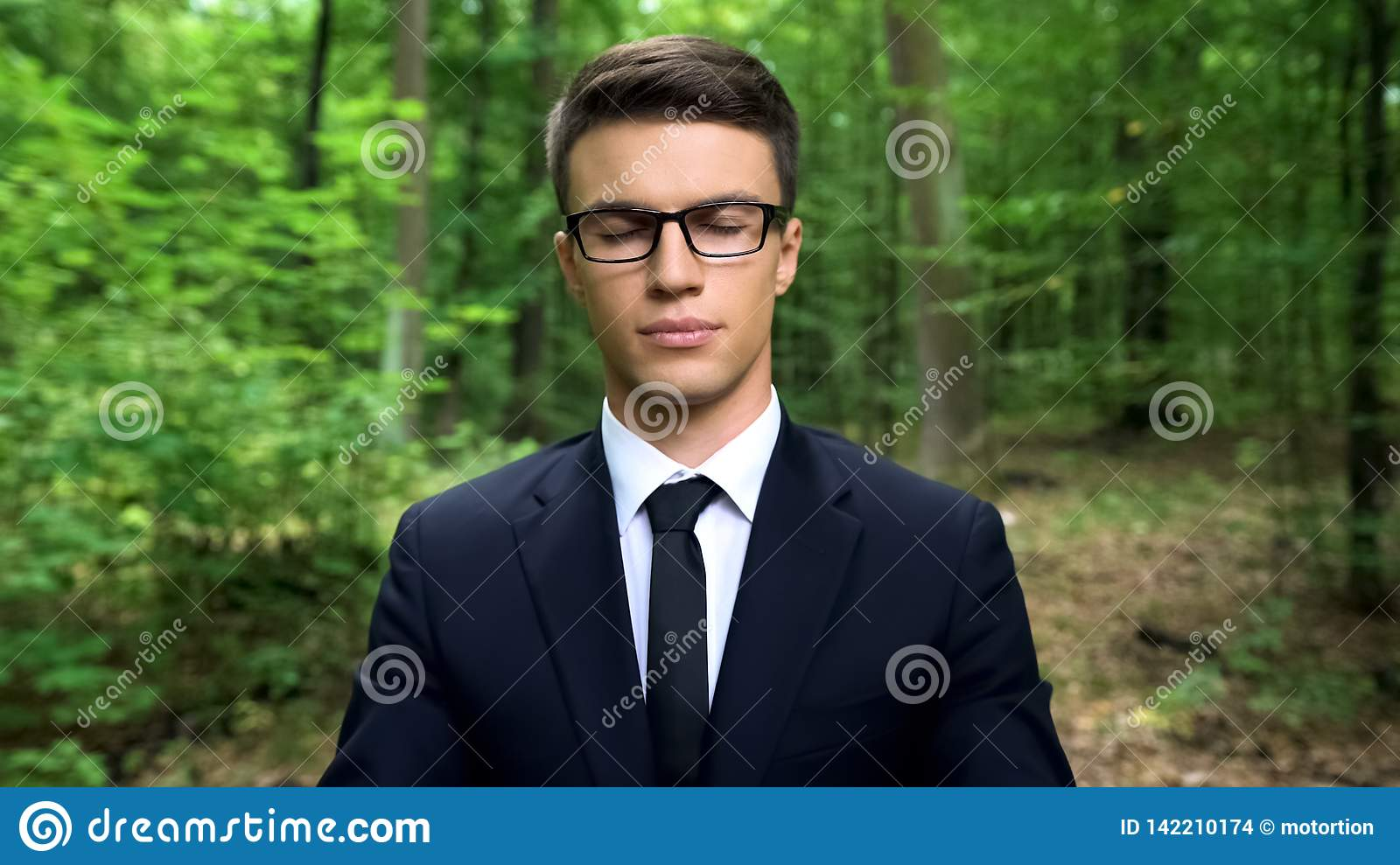 Business person feeling inner harmony in forest, finding body and mind balance
