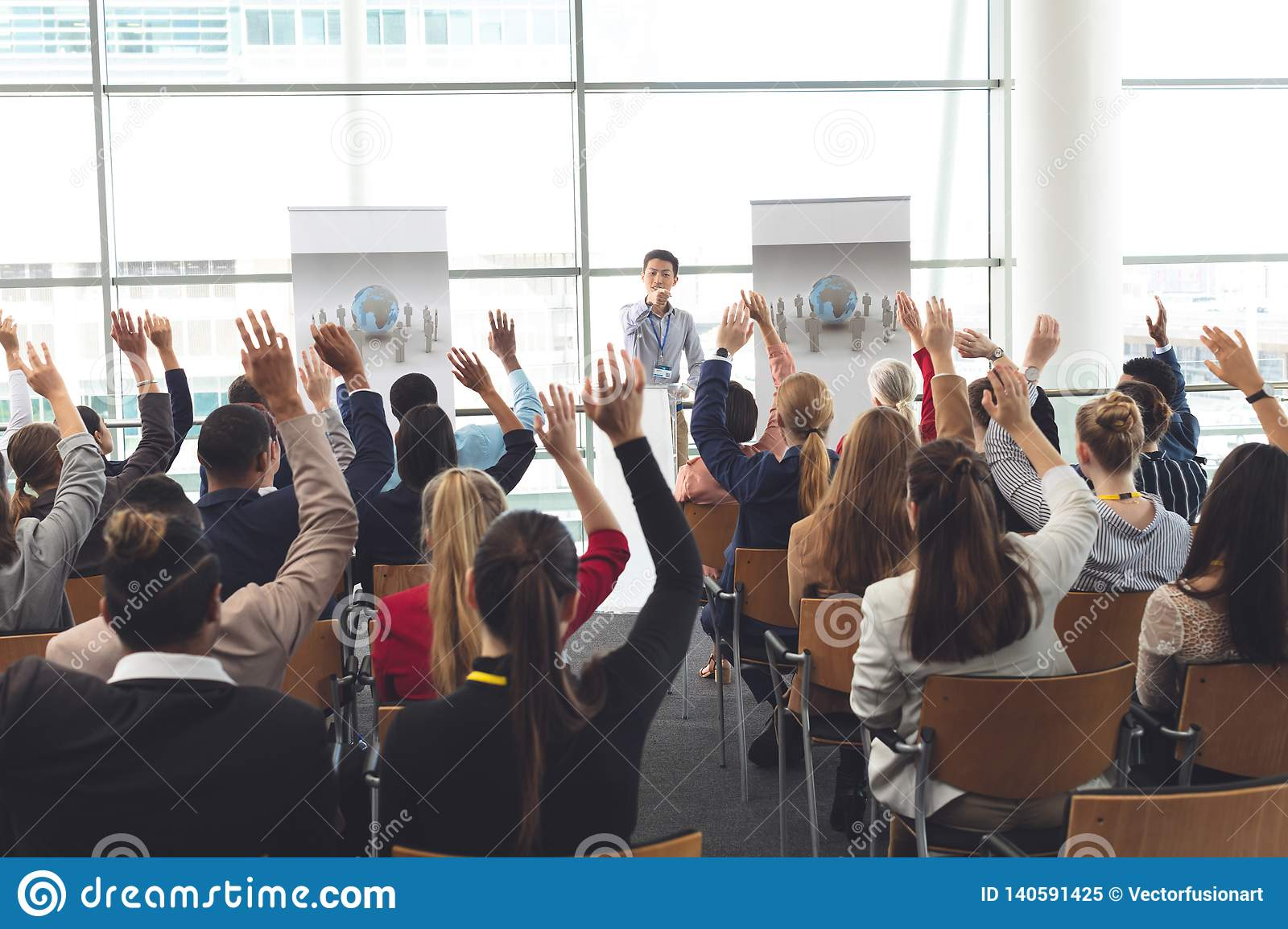 Business professionals raising hands in a business seminar
