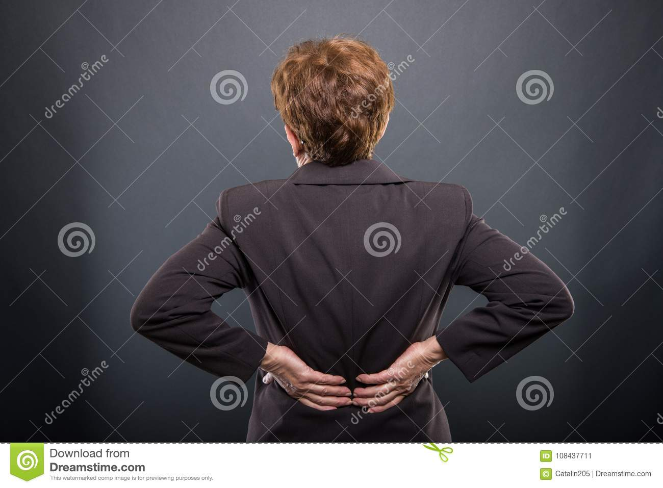 Business senior lady holding her back like hurting