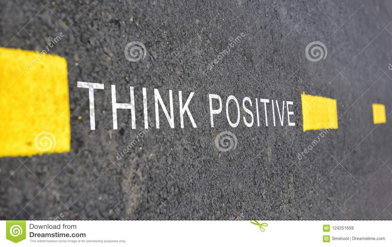 Words of Think positive with yellow line marking on road surface