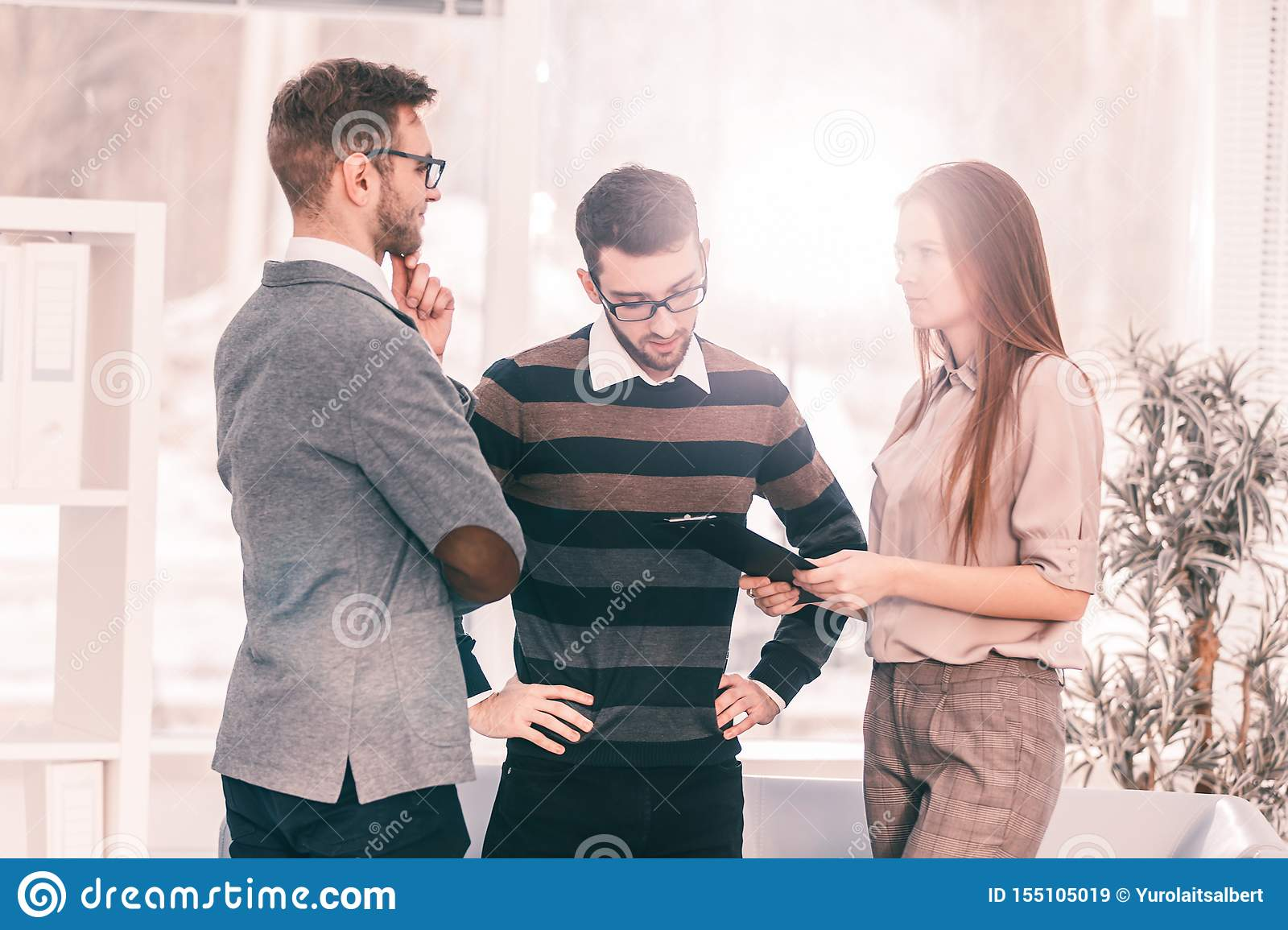 Business team discussing working papers in the lobby of the modern office