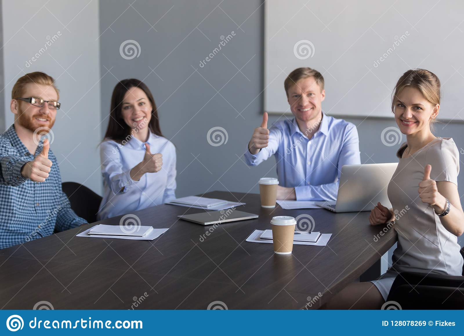 Business team looking at camera showing thumbs up at meeting