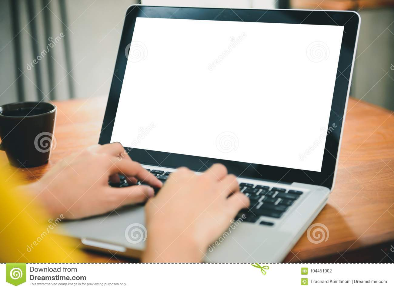 Woman hands typing laptop computer with blank screen on table in coffee shop.