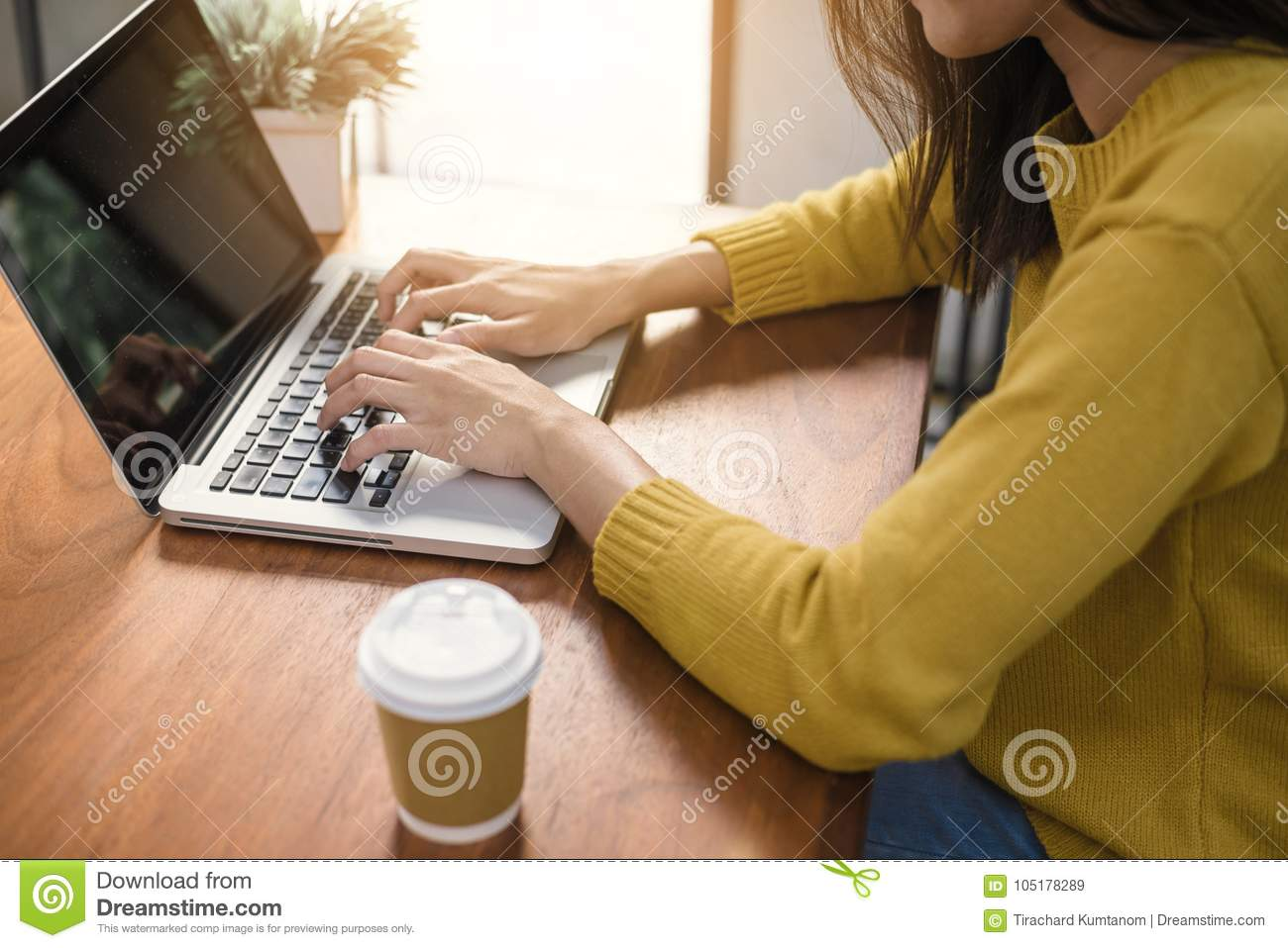 Digital lifestyle working outside office. Woman hands typing laptop computer with blank screen on table in coffee shop.