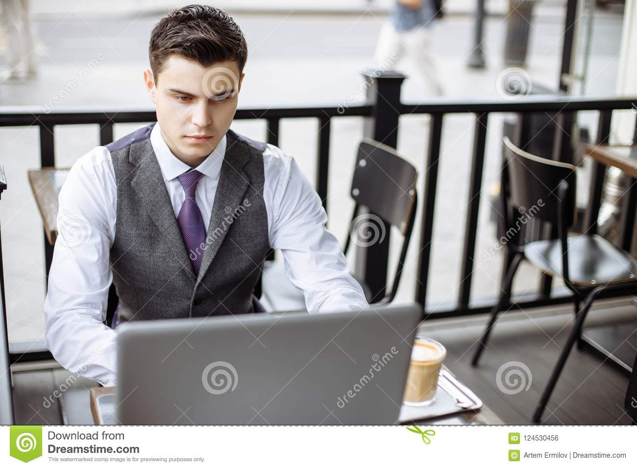 Business, technology and people concept - young man with a laptop and coffee cup at city street cafe