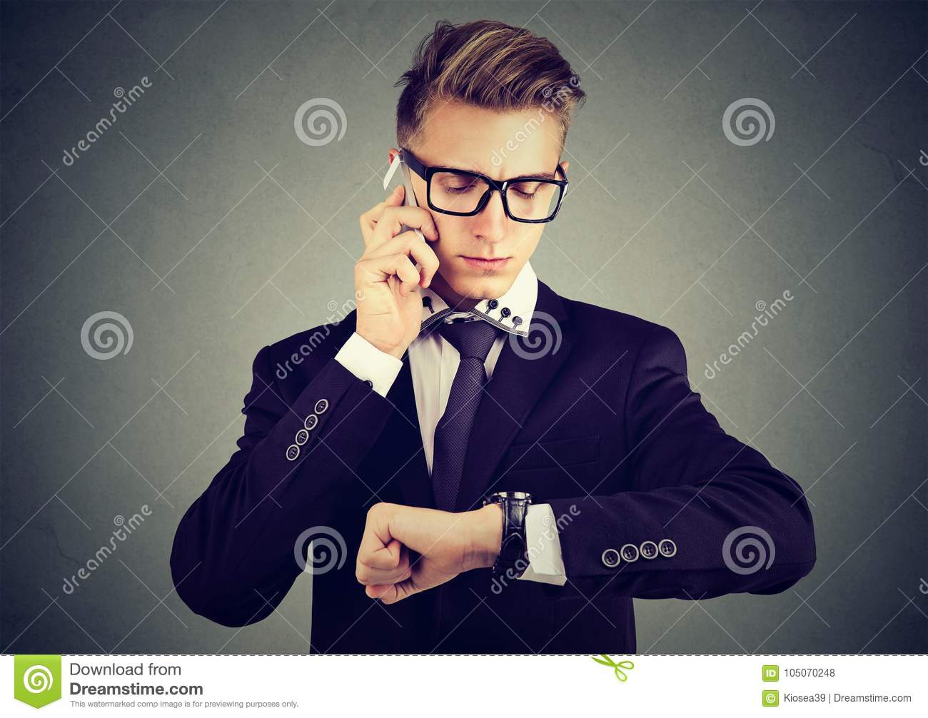 Businessman looking at wrist watch, talking on mobile phone.