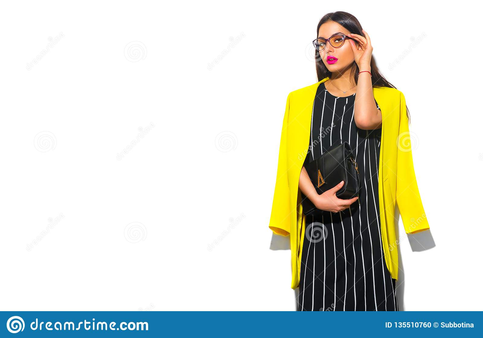 Business wear look style. Beauty fashion model girl in trendy yellow blazer wearing glasses, on white background