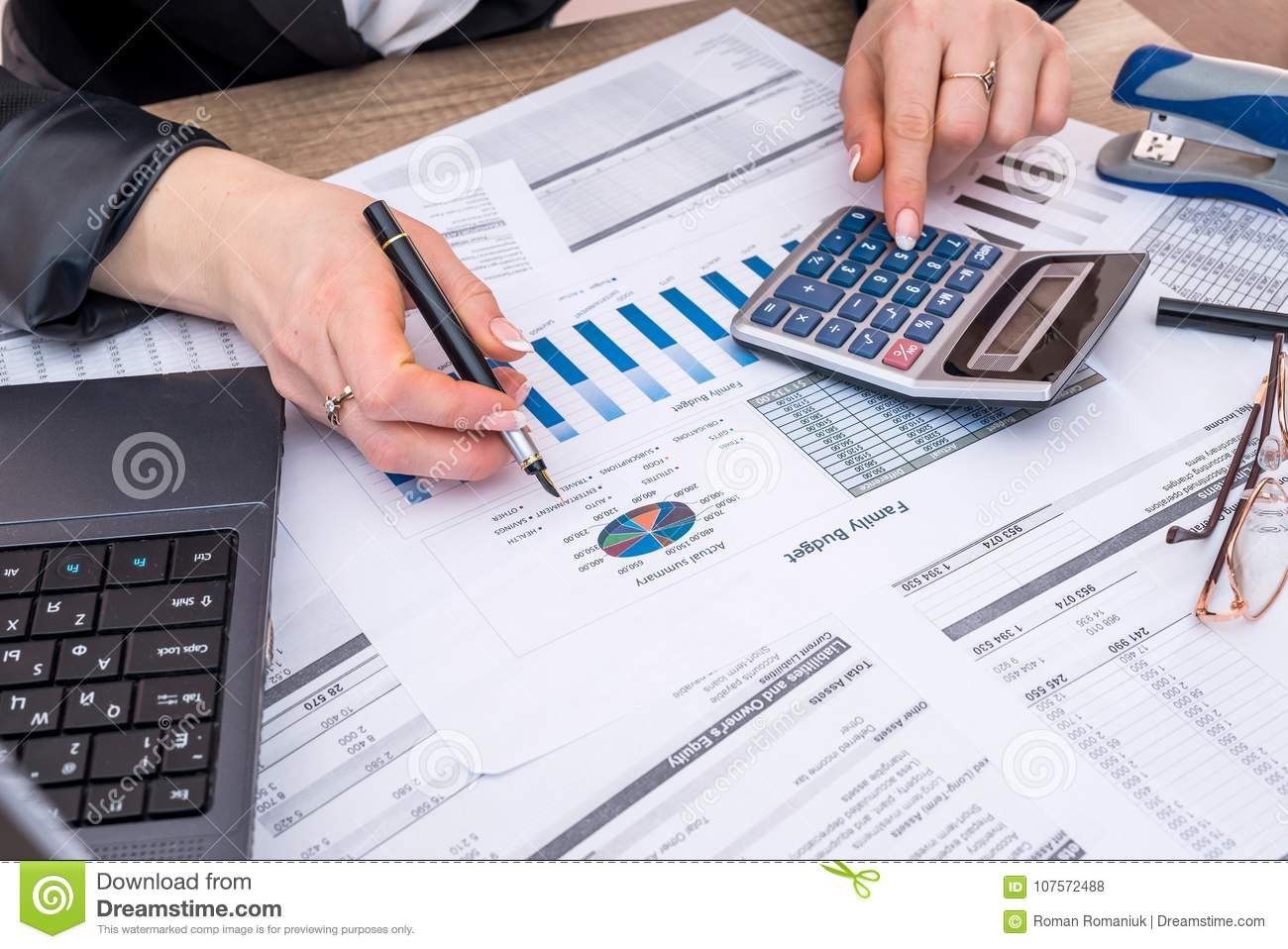 Business woman account annual budget with laptop, pen