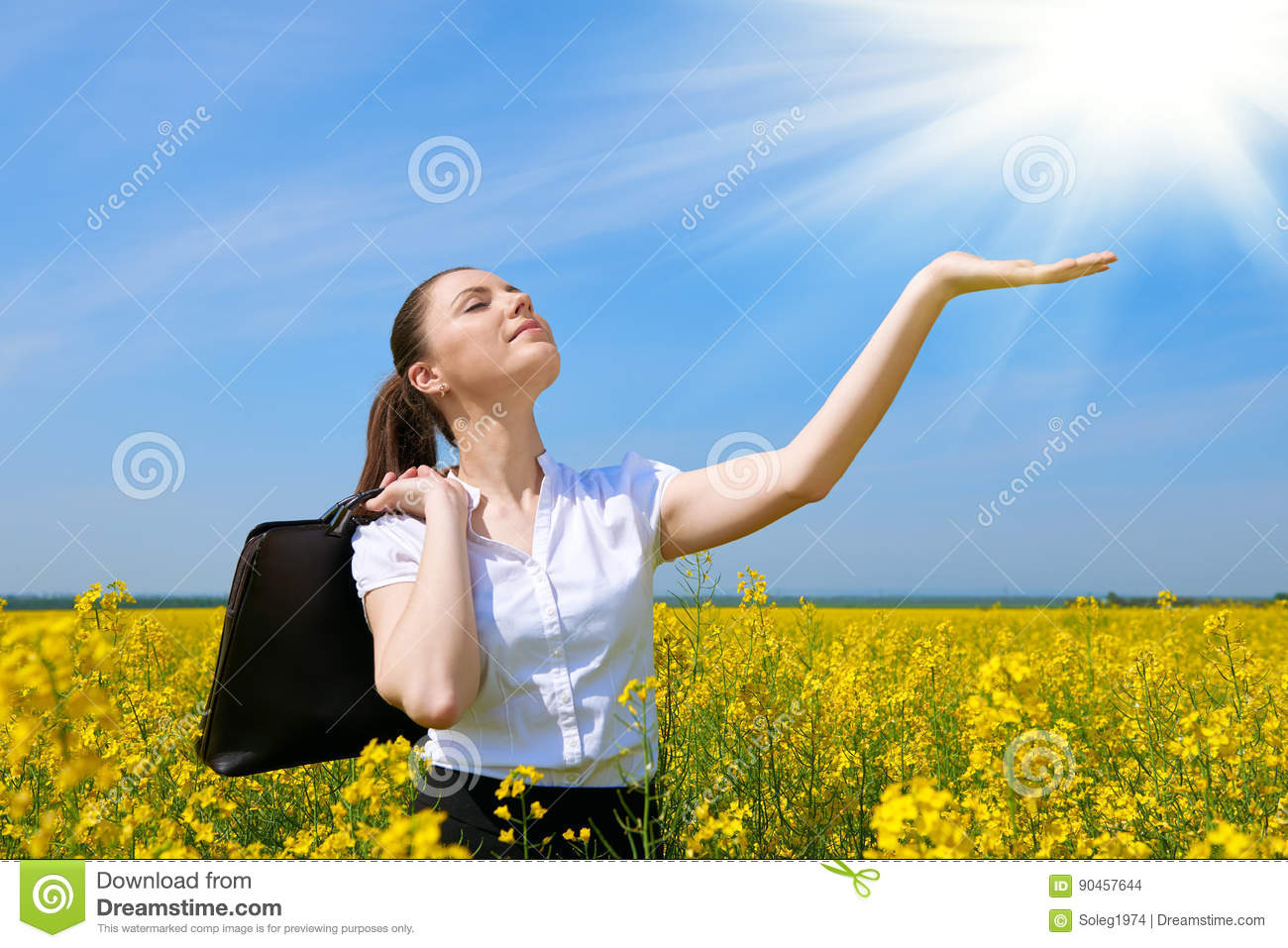 Business woman with briefcase relaxing in flower field outdoor under sun. Young girl in yellow rapeseed field. Beautiful spring la