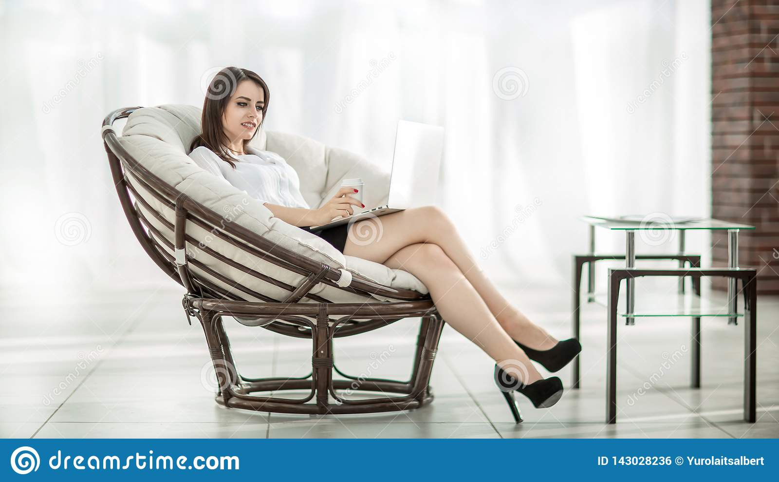 Business woman with documents sitting round a comfortable chair