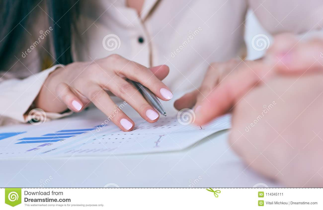 Business woman hand holding pen and pointing at financial diagram, graph during conference sitting at the office desk.
