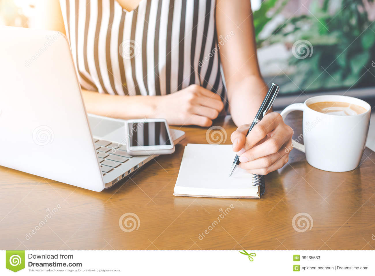 Business woman hand working at a computer and writing on a noteped with a pen.