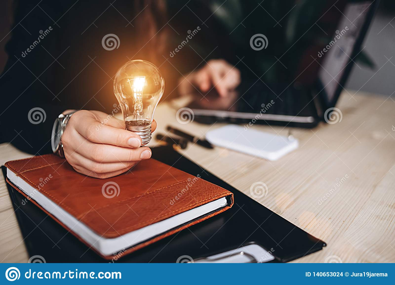 Business Woman holding light bulbs on the desk in an office and works on computer.