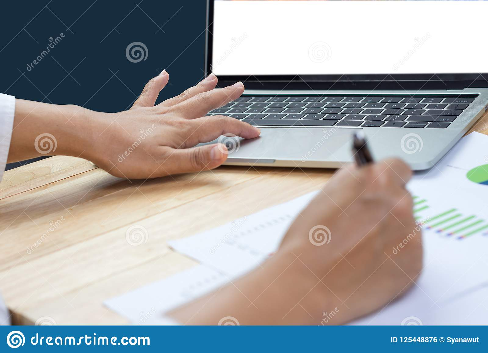 Business woman holding pen in hand working with financial paper charts and laptop computer