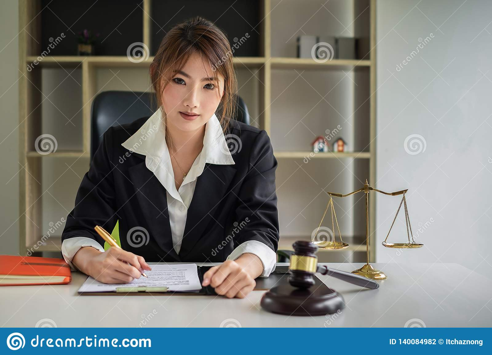 Business woman or lawyers discussing contract papers with brass scale on wooden desk in office. Law, legal services, advice,