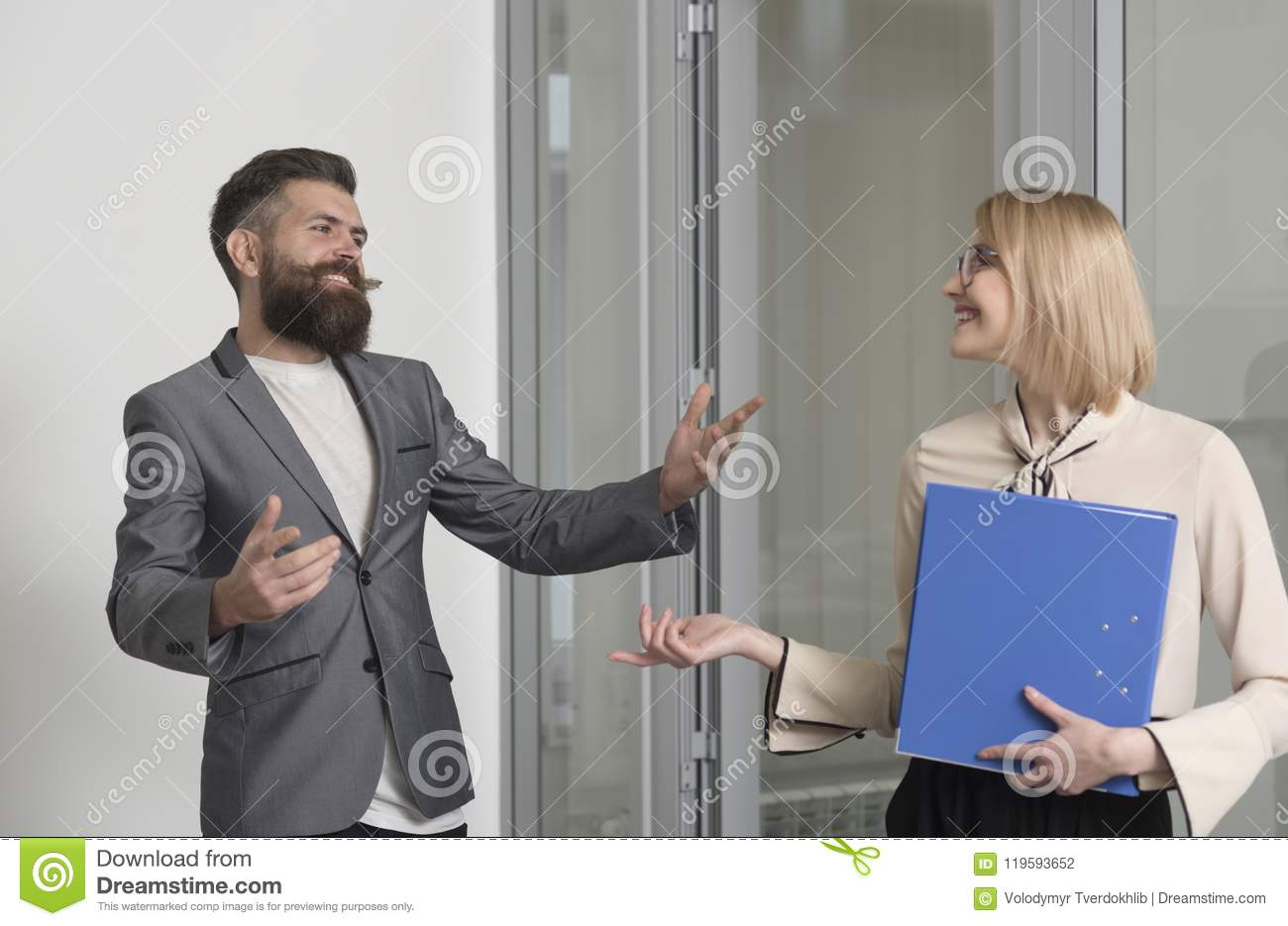 Business woman and man colleagues in office. Bearded man talk to sensual woman with binder. Office workers wear formal