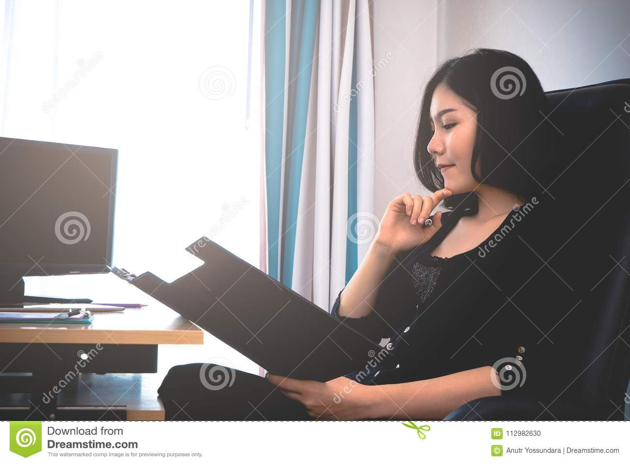 Business woman reading business report in office