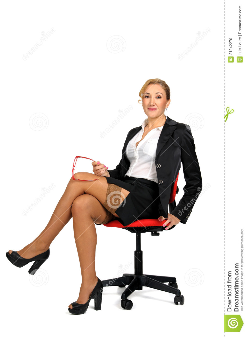 Sexy business woman seated in a chair isolated in white.