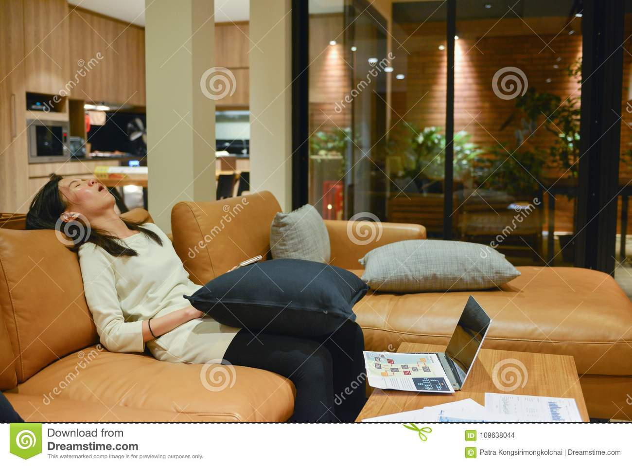 Business Woman Sleeping On Sofa In Living Room At Night.