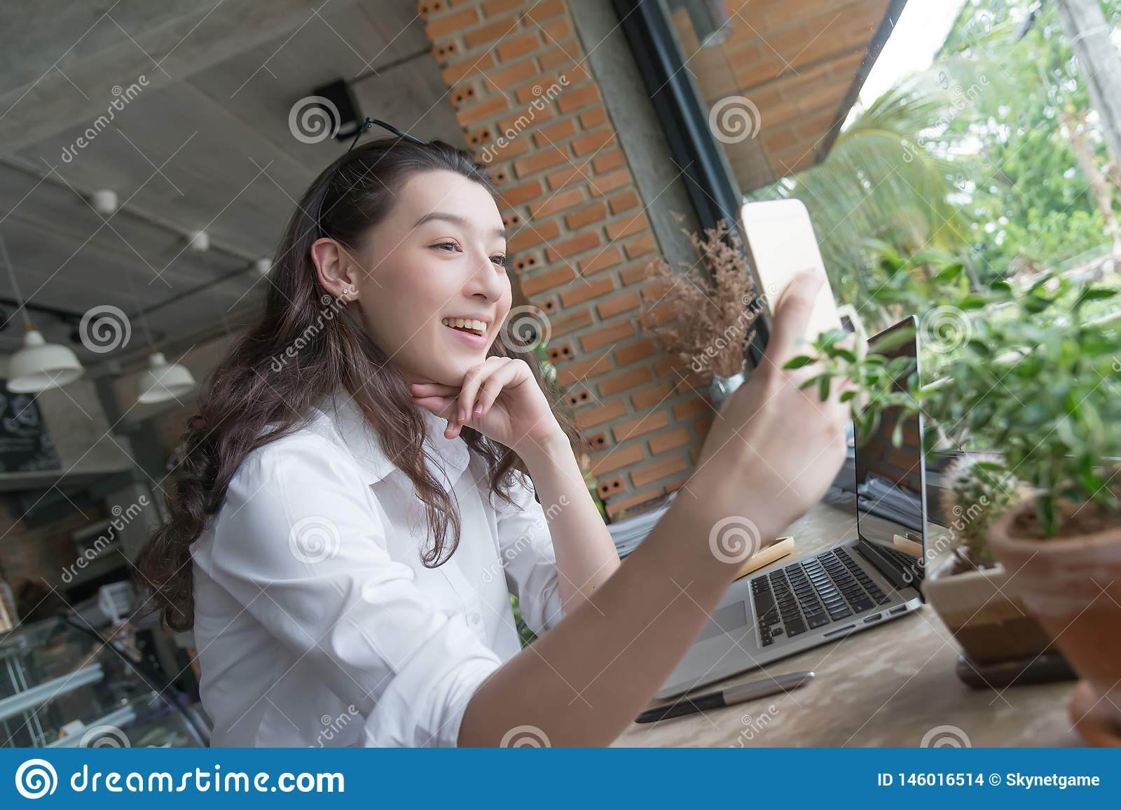 Business woman taking selfie on the Smart phone in coffee break time at her work place.young business online marketing concept