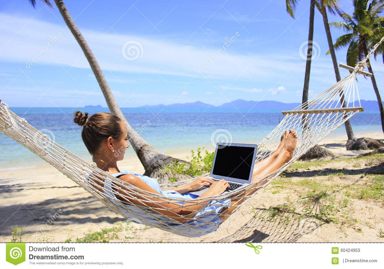 Business Woman Working In A Hammock On The Beach Stock