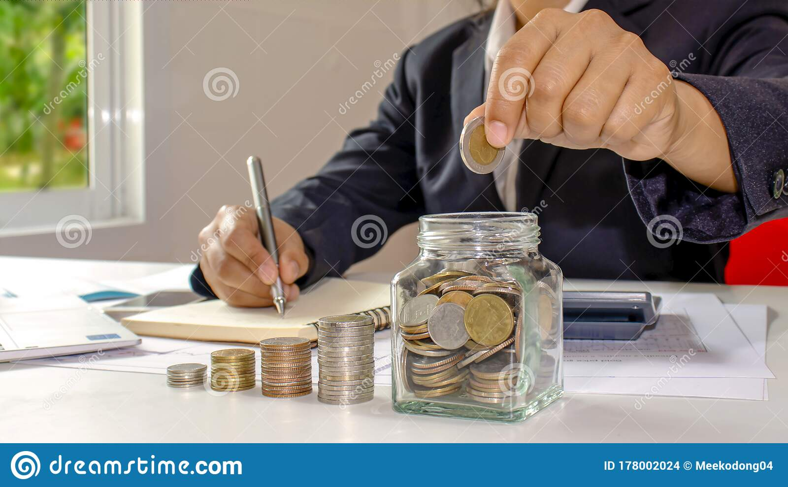 Business Women Who Are Putting Coins In A Jar Of Money Including A Notebook On A Wooden Desk For Work Ideas For Saving Money Stock Photo Image Of Accounting Debt 178002024