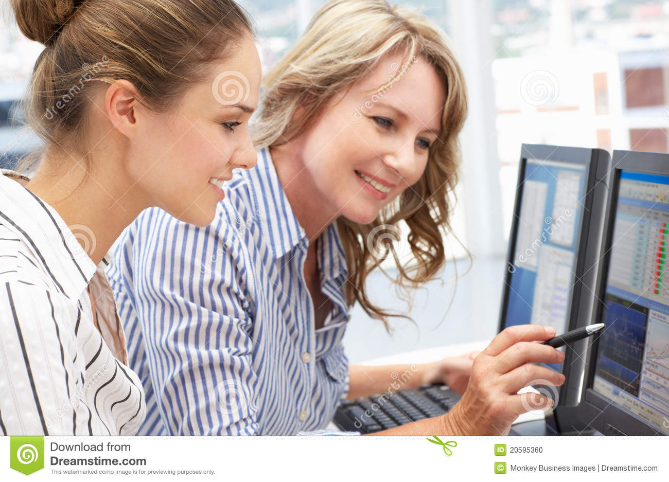 Business women working together on computers