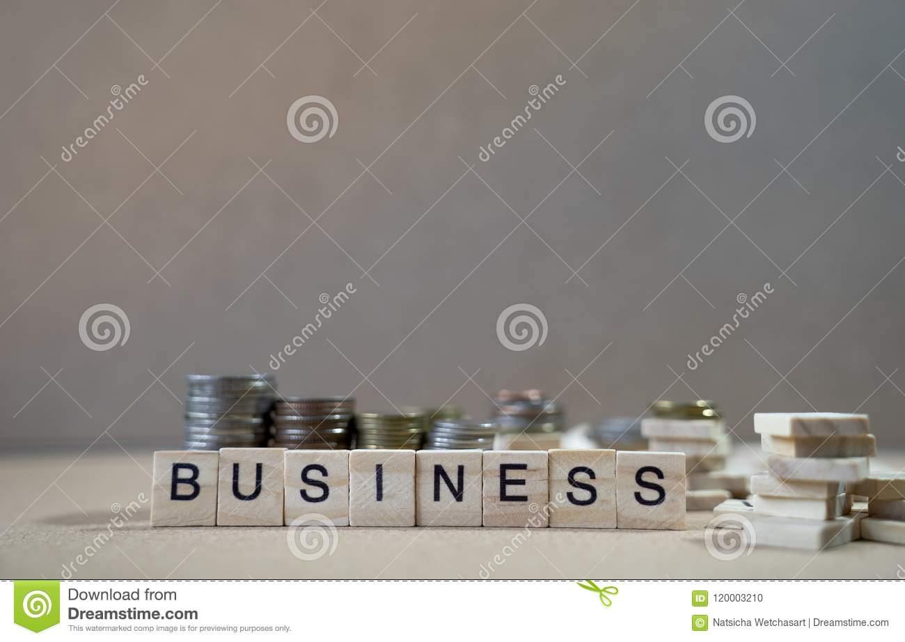 Business Word Written In Wooden Cube on wood table with money gr