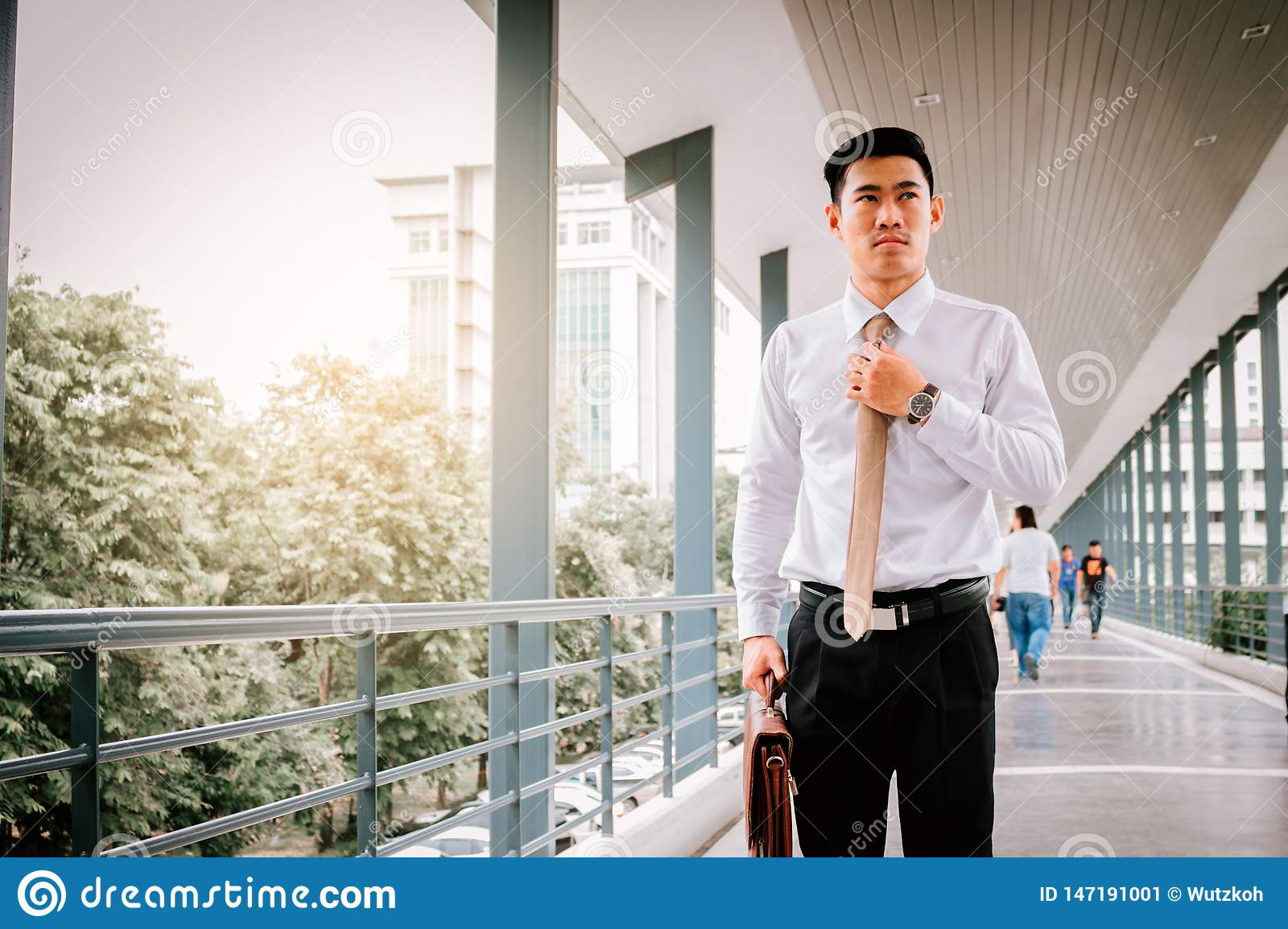 Businessman adjusting necktie before working time
