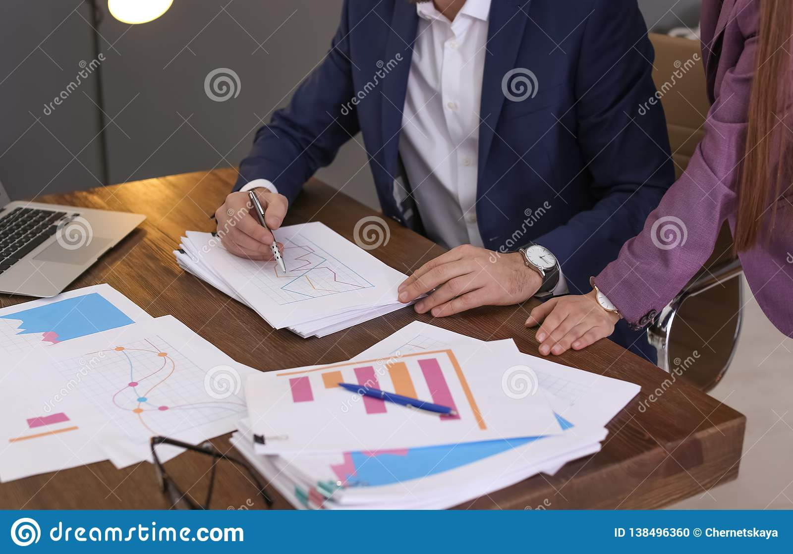 Businessman and assistant working with documents at table