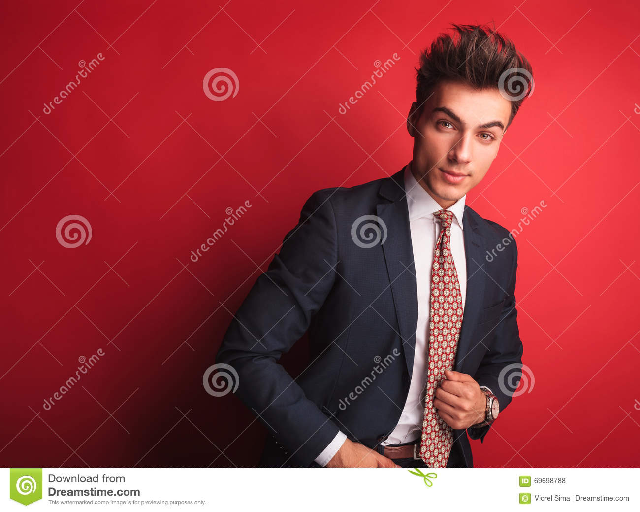 3140327c6525 Portrait young businessman in black suit with red tie, posing in red studio  background while looking at the camera. he is leaning on side with one hand  in ...