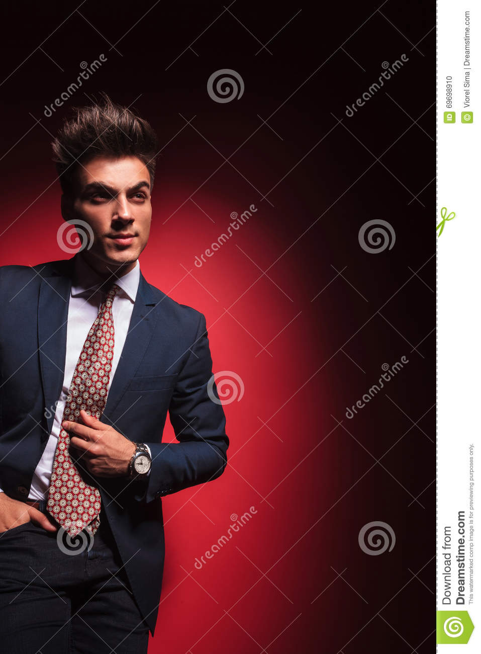 d98f3b9b6be0 Smart casual young businessmanwith red tie posing standing in red studio  background . with hand in pocket fixing his tie while looking away from the  camera