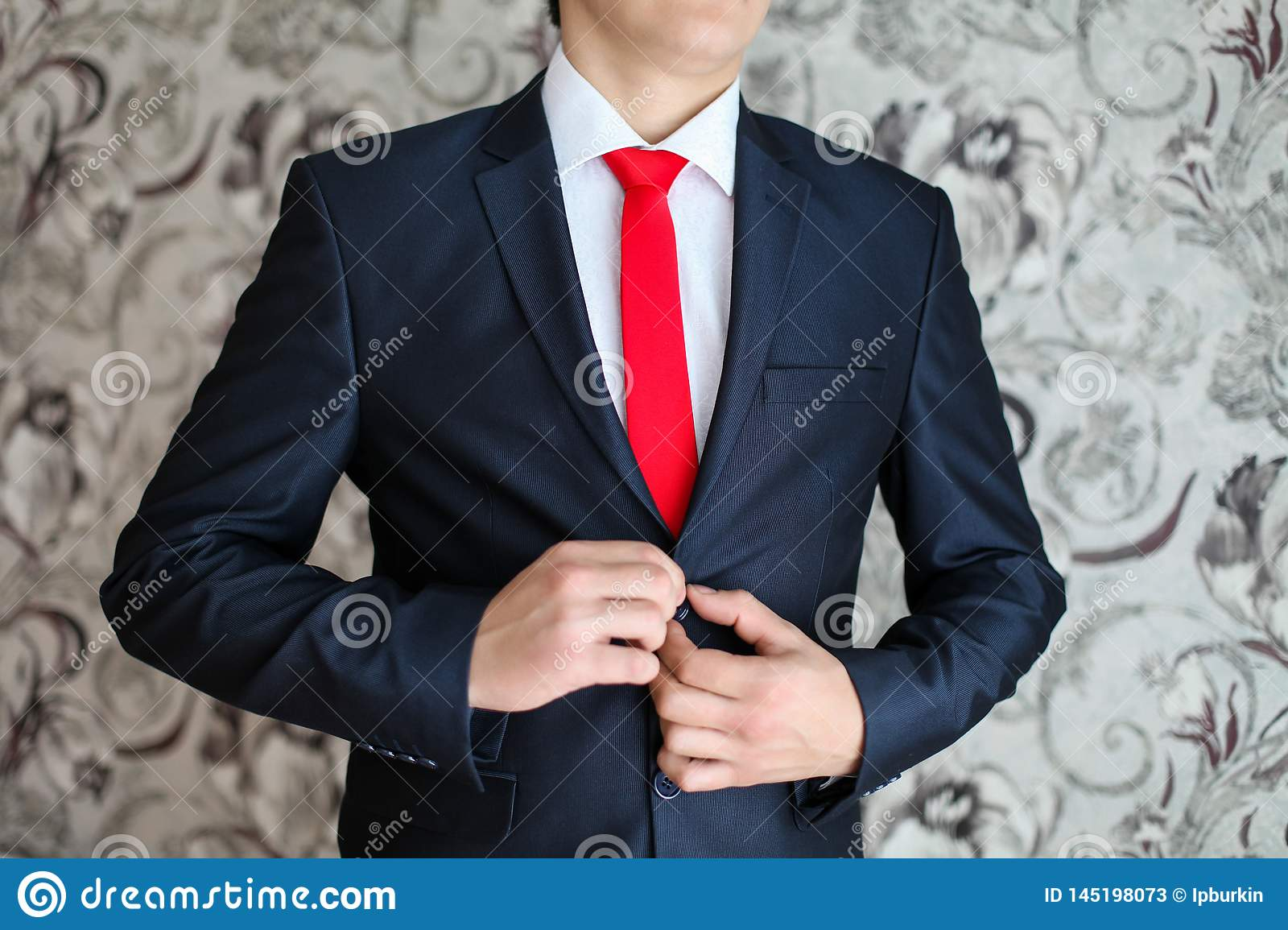 Businessman in black suit and a red tie. Smart casual outfit. Man getting ready for work. groom in a jacket, the groom fastens his