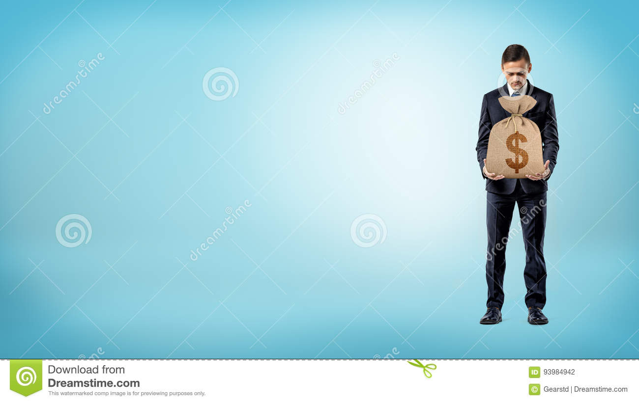 A businessman on blue background holding a burlap money bag with a dollar sign on it.