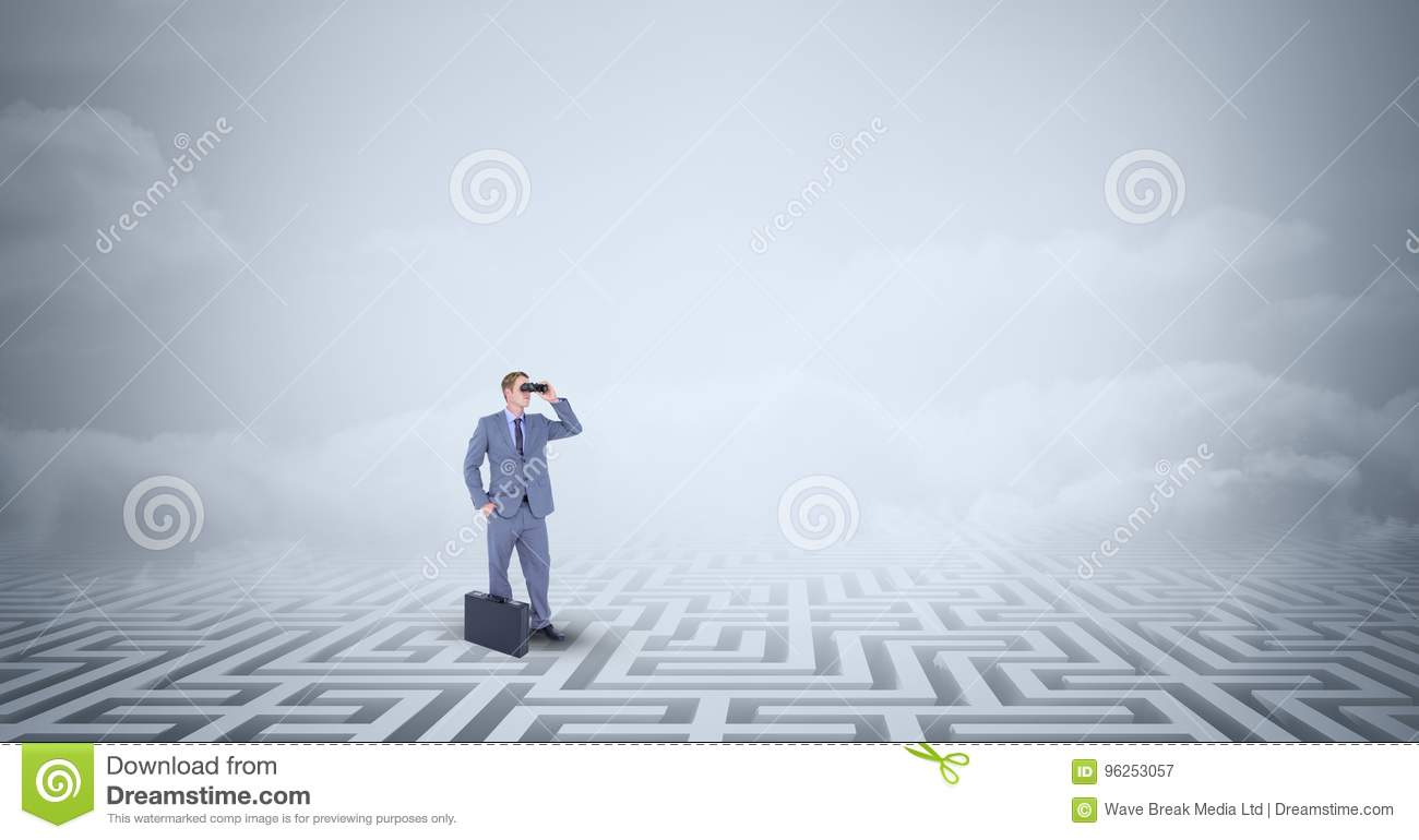 Businessman with briefcase standing lost in maze