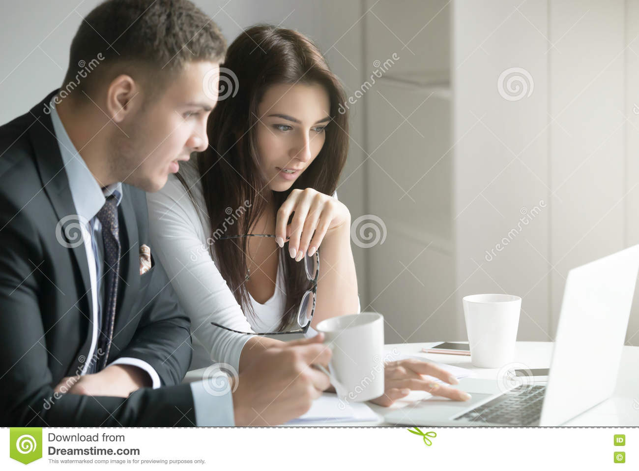Businessman and businesswoman at office desk, looking at the lap