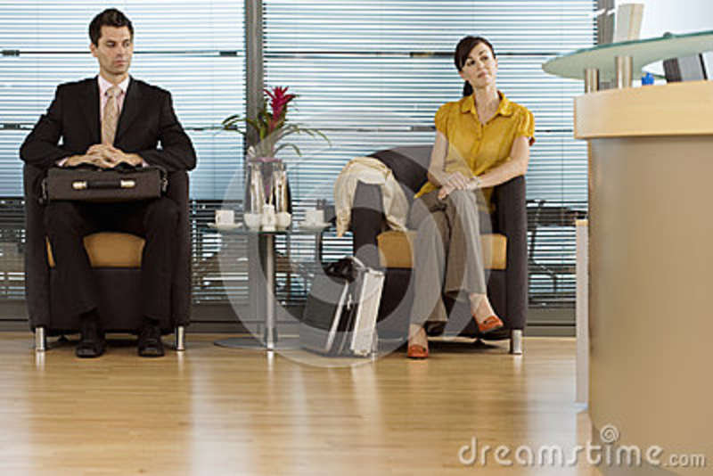 Businessman and businesswoman sitting in office reception area, waiting patiently
