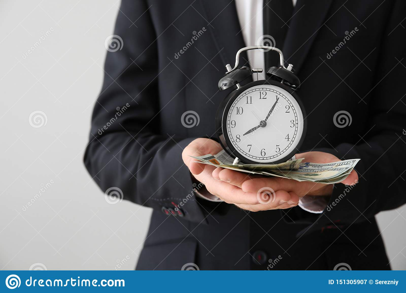 Businessman with clock and money on light background, closeup