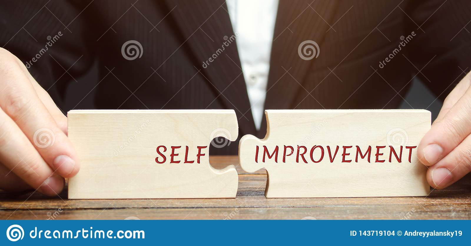 Businessman collects puzzles with the word Self-improvement. Concept of new business skills and motivation. Personal and career