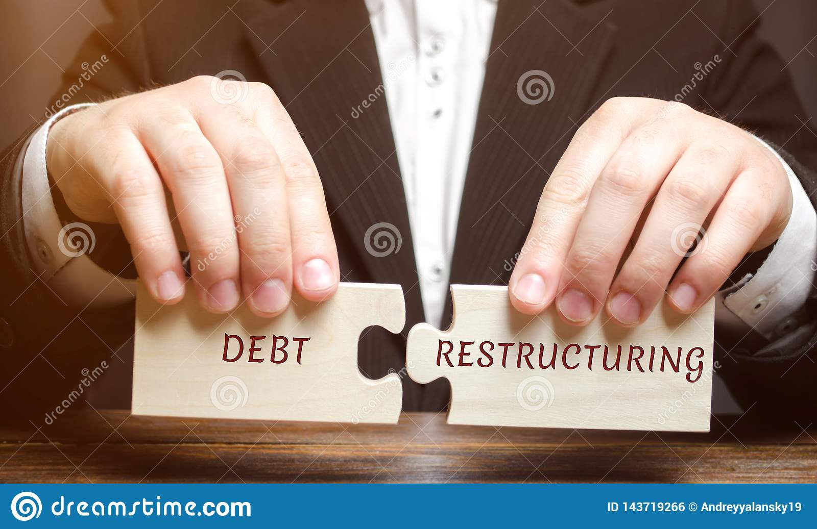 Businessman collects wooden blocks with the word Debt Restructuring. Debts relief. Changing loan repayment terms. Changing the